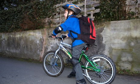a little boy on a bicycle, going to school, wearing a safety helmet and protective pads